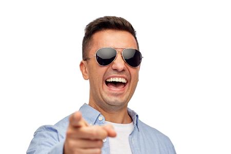 caras felices: verano, estilo, las emociones y la gente concepto - riendo hombre en gafas de sol que señala el dedo en usted