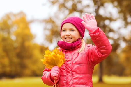 autumn, childhood, happiness and people concept - happy beautiful little girl with maple leaves bunch waving hand outdoors