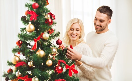 decorating christmas tree: family, x-mas, winter holidays and people concept - happy couple decorating christmas tree at home