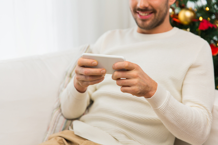 new age: christmas, technology, people and holidays concept - close up of smiling man with smartphone at home