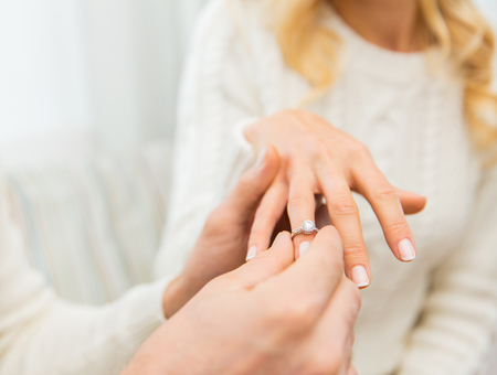 diamond ring: love, couple, relationship and holidays concept - close up of man giving diamond ring to woman