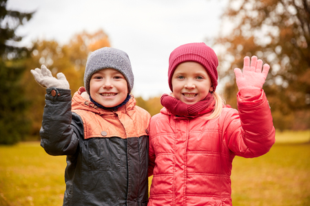 two boys: childhood, leisure, friendship, autumn and people concept - happy little girl and boy waving hands in park Stock Photo