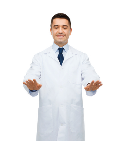 imaginary: healthcare, profession, people and medicine concept - smiling male doctor in white coat touching something imaginary