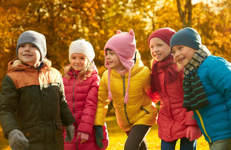 leisure games: childhood, leisure, friendship and people concept - group of happy kids playing game and having fun in autumn park