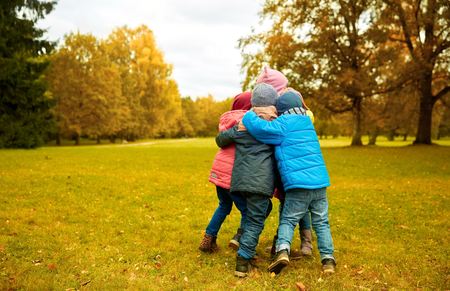 kids hugging: childhood, leisure, friendship and people concept - group of happy kids hugging in autumn park
