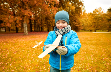 fun activity: autumn, childhood, dream, leisure and people concept - happy little boy playing with wooden toy plane outdoors