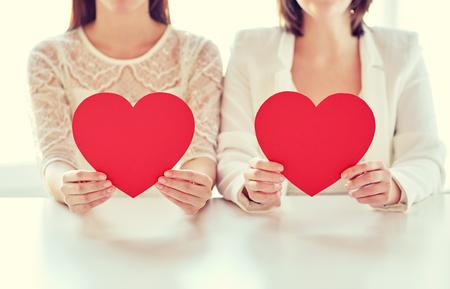 matrimonio feliz: personas, la homosexualidad, el matrimonio entre personas del mismo sexo, las vacaciones y el concepto de amor - cerca de la feliz pareja de lesbianas que llevan a cabo corazones de papel rojo Foto de archivo