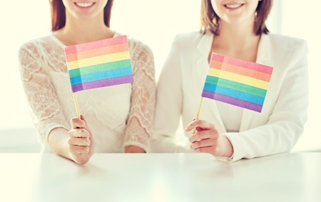 lesbian: people, homosexuality, same-sex marriage, gay pride and love concept - close up of happy lesbian couple holding rainbow flags