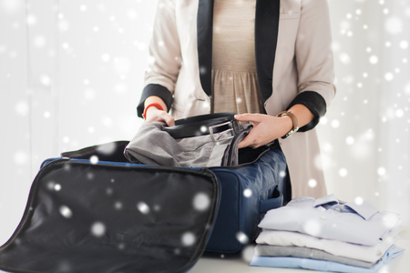 trip over: business, trip, luggage and people concept - close up of woman formal male clothes into travel bag at home over snow effect Stock Photo