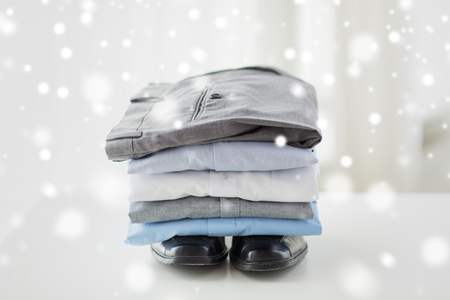 ironed: business, clothes, housekeeping and objects concept - close up of ironed and folded shirts, trousers and formal shoes on table at home over snow effect