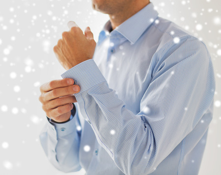formal dressing: people, business, fashion and clothing concept - close up of man fastening buttons on shirt sleeve at home over snow effect Stock Photo