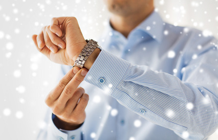 fastening: people, business, accessories and clothing concept - close up of man in shirt fastening wristwatch at home over snow effect