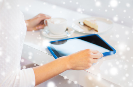 leisure time: leisure, people, technology and lifestyle concept - close up of young woman hands with tablet pc computer drinking coffee and eating cake at cafe over snow effect Stock Photo
