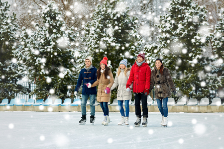 patín: gente, invierno, la amistad, el deporte y el concepto de ocio - amigos felices de patinaje sobre hielo en la pista de patinaje al aire libre