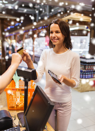 shopping card: sale, shopping, consumerism and people concept - happy young woman with credit card and wallet buying food at checkout in market over snow effect