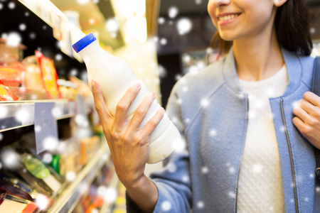 hand holding bottle: sale, shopping, consumerism, food and people concept - close up of happy young woman holding milk bottle in market or grocery store over snow effect