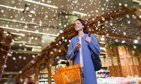 consumerism: sale, shopping, consumerism and people concept - happy young woman with food basket in market over snow effect
