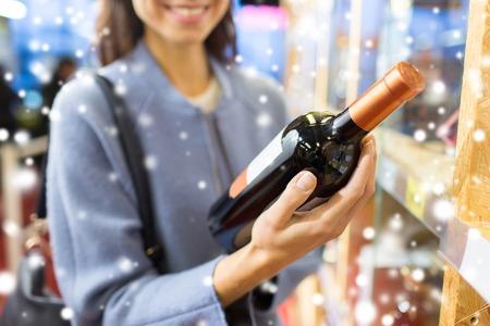 jovenes tomando alcohol: venta, las compras, el consumismo y la gente concepto - mujer joven feliz elegir y comprar vino en el mercado o tienda de licores m�s de efecto de nieve