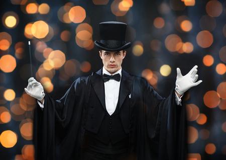 rendimiento, circo, espectáculo concepto - mago en el sombrero de copa y capa mostrando truco con la varita mágica sobre fondo luces cerca Foto de archivo