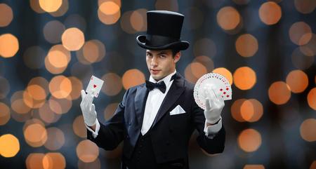 la magia, el rendimiento, los juegos de azar, casino, las personas y concepto de espectáculo - mago en la parte superior que muestra el sombrero truco con cartas de juego sobre el fondo luces cerca Foto de archivo