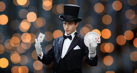magic, performance, gambling, casino, people and show concept - magician in top hat showing trick with playing cards over nigh lights background Stock Photo