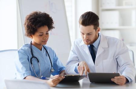 ziekenhuis, beroep, mensen en geneeskunde concept - twee artsen met een tablet pc computer vergadering en praten op medische kantoor