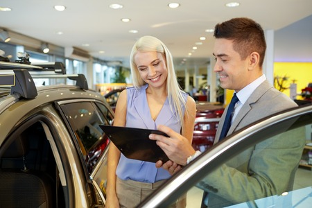 car rent: auto business, car sale, consumerism and people concept - happy woman with car dealer in auto show or salon Stock Photo