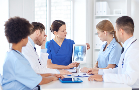people on computers: profession, people, surgery, radiology and medicine concept - group of doctors with x-ray on tablet pc computer screen meeting at medical office Stock Photo