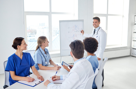 learning concept: medical education, health care, medical education, people and medicine concept - group of happy doctors or interns with mentor meeting and drawing on flip board at hospital