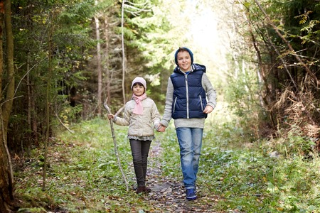 younger: childhood, hiking, family, friendship and people concept - two happy kids walking along forest path