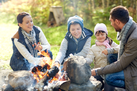 marshmallows: camping, travel, tourism, hike and people concept - happy family roasting marshmallow over campfire Stock Photo