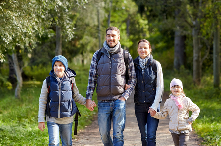 in the woods: adventure, travel, tourism, hike and people concept - happy family walking with backpacks in woods
