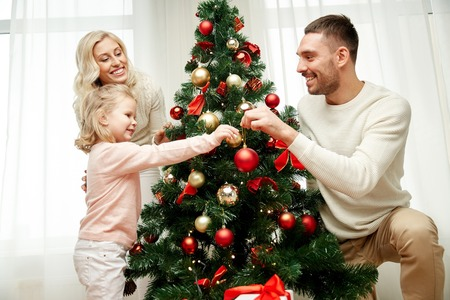 home decorating: family, x-mas, winter holidays and people concept - happy mother, father and little daughter decorating christmas tree at home