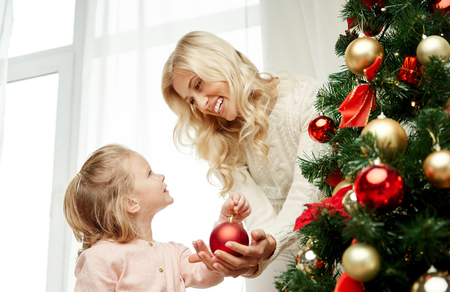 decorate: family, x-mas, winter holidays and people concept - happy mother and little daughter decorating christmas tree at home