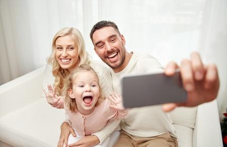 días de fiesta, la tecnología y las personas concepto - la familia feliz que se sienta en el sofá y la toma de fotografías selfie con el teléfono inteligente en el hogar