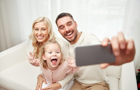 holidays, technology and people concept - happy family sitting on sofa and taking selfie picture with smartphone at home