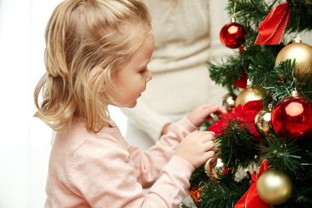 decorating christmas tree: family, x-mas, winter holidays and people concept - happy  little girl decorating christmas tree  with mother at home Stock Photo