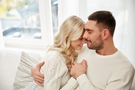家族、愛、冬、休日、人コンセプト - 格子縞自宅のソファの上に座ってで覆われて幸せなカップル