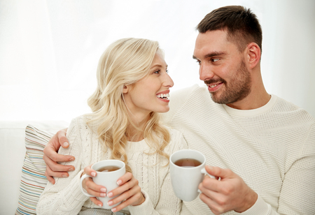couple talking: family, winter, holidays, love and people concept - happy couple with cups drinking tea and sitting on sofa at home