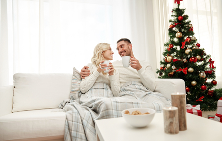 romantic couples: family, christmas, holidays, love and people concept - happy couple covered with plaid drinking tea and sitting on sofa at home