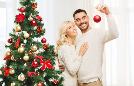 home decorating: family, x-mas, winter holidays and people concept - happy couple decorating christmas tree with ball at home