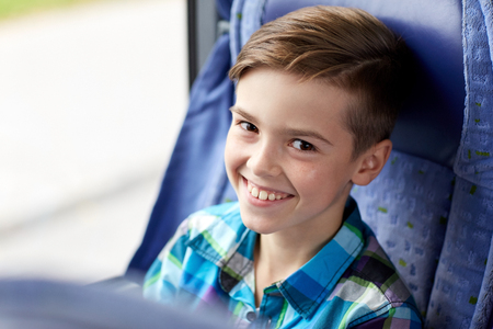 bus: transport, tourism, road trip and people concept - happy boy sitting in travel bus or train