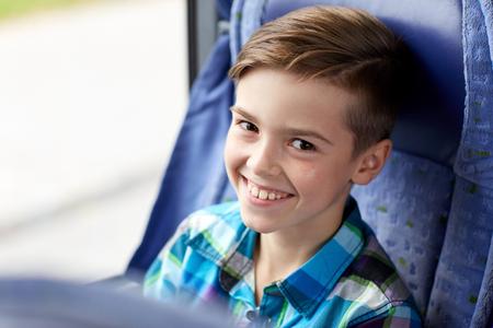 transport, turystyka, podróż drogi i ludzie koncepcja - szczęśliwy chłopiec siedzi w autobusie lub pociągu podróży