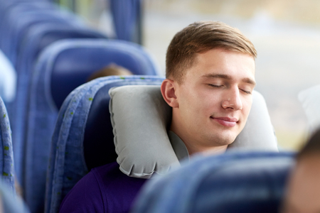 transport, tourism, road trip and people concept - happy young man sleeping in travel bus with pillow