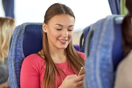 transporte, turismo, viaje por carretera y la gente concepto - mujer joven feliz sentado en el autobús de viaje con teléfono inteligente