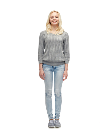 skinny jeans: female, gender, fashion and people concept - smiling young woman or teenage girl in gray pullover and jeans