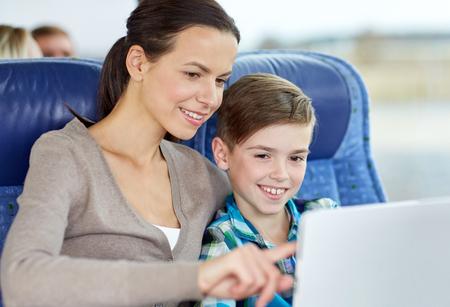 passenger buses: los viajes, el turismo, la familia, la tecnología y la gente conceptuales - feliz madre e hijo con el ordenador Tablet PC que se sientan en autobús o tren viajes Foto de archivo