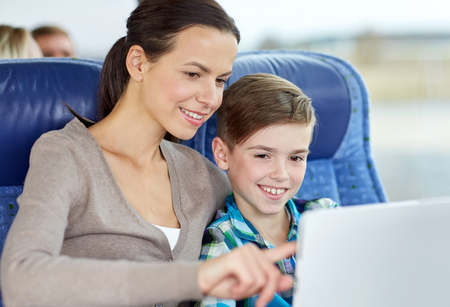 single parent family: travel, tourism, family, technology and people concept - happy mother and son with tablet pc computer sitting in travel bus or train