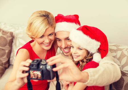 merry chrismas: family, christmas, x-mas, winter, happiness and people concept - smiling family in santa helper hats taking picture with photo camera Stock Photo