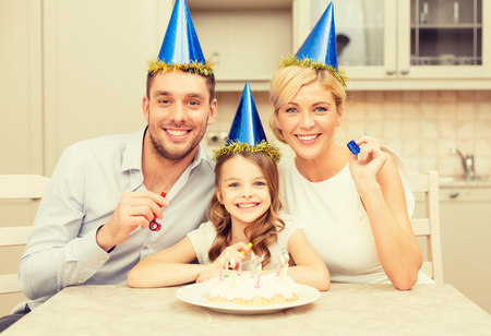 favor: celebration, family, holidays and birthday concept - happy family in blue hats with cake and candles blowing favor horns
